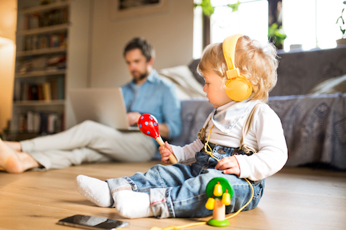 Young father at home sitting on wooden floor, working on laptop, his cute little son with smart phone and earphones, listening music, playing with musical instruments.